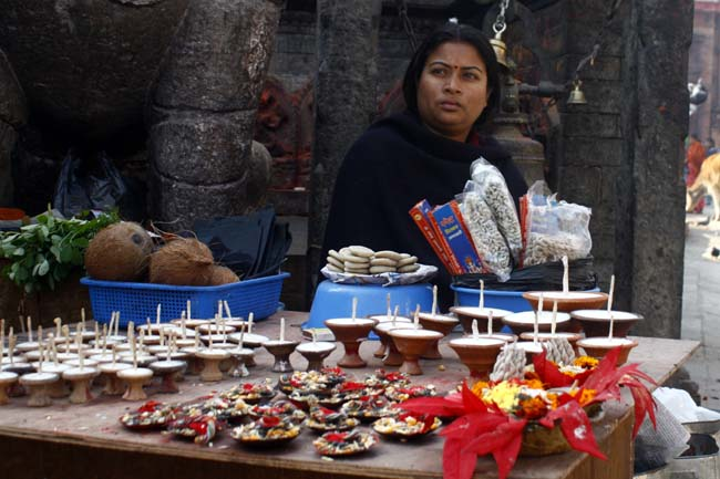 01 Woman with worship accessories on her street stall in Basantapur