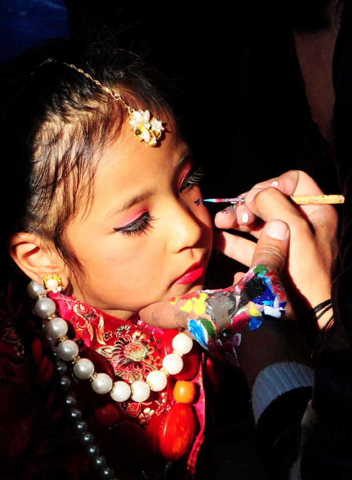 A cute girl of Tamang Ethnic Community in Nepal, making face paint on the occasion of Lhosar Celebration. I have captured this beautiful snap at Tundikhel, Kathmandu