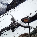 A signpost for trekkers placed on the height of 4919 meters above the sea level on the way to Tilicho Lake