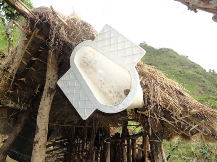 """Toilet Pan distributed under """"Khulla Disa Mukta Program"""" hanging on the roof of cattle pen of Rita Chepang, resident of Metrang VDC Kaule Chitwan"""